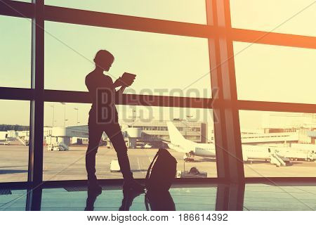 businesswoman using tablet computer at the airport. silhouette of a girl traveler with backpack. business and travel