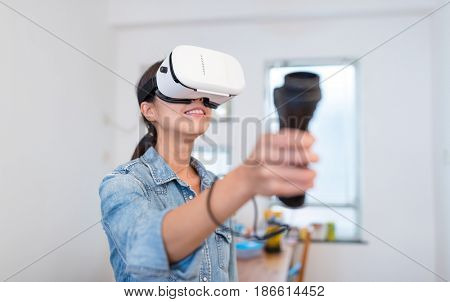 Woman play game with virtual reality device and joystick at home