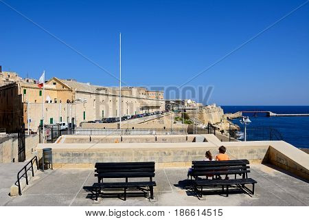 VALLETTA, MALTA - MARCH 30, 2017 - View from the Siege Memorial towards north along Triq Il-Mediterran with a couple sitting on a bench looking at the view in the foreground Valletta Malta Europe, March 30, 2017.