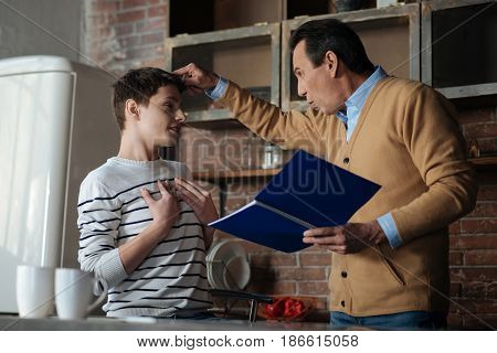 Should study better. Smiling teenager putting both hands on his chest while turning head to his father and looking at him
