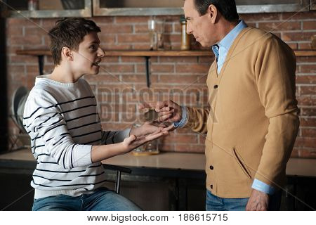 Listen to me. Strict man standing in semi position opposite his son while pointing and looking at him