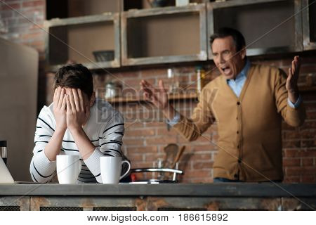 Do not shout at me. Upset teenager putting elbows on the table and hiding his face while turning away from his parent