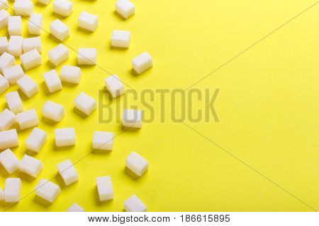 Sugar cubes scattered on a yellow background with an empty space for text copy paste