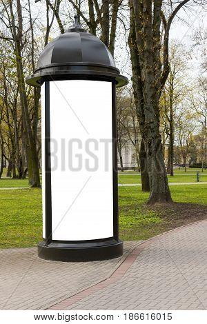 Advertising column mockup. Blank public information board mock up near the park.