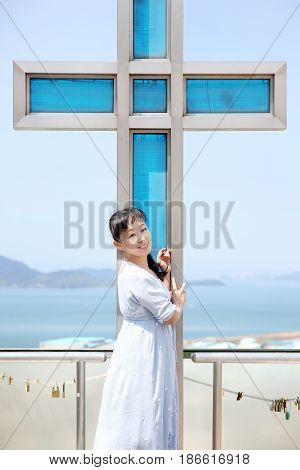 Portrait of young japanese woman with metal cross