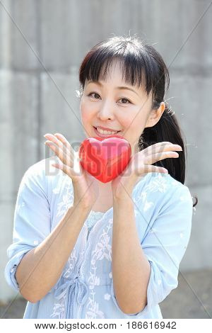 Portrait of young japanese woman hand holding red heart