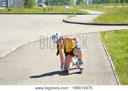 Little girl in helmet on the skates. sports child rollerskating in the city