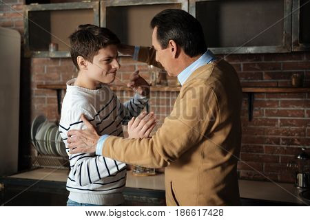 Put up with rudeness. Angry teenager pressing his lips and raising arms while looking at his father