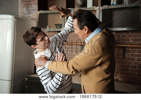 Defend himself. Strict male person raising both arms while attacking his son, standing in semi position