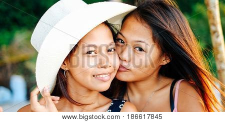 Portrait of two happy female Asian sisters on beach