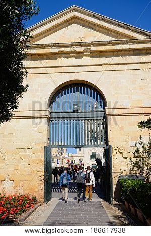 VALLETTA, MALTA - MARCH 30, 2017 - Tourists walking through an archway in the Upper Barrakka Gardens towards Castille Square Valletta Malta Europe, March 30, 2017.
