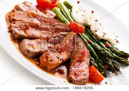 Grilled meat with asparagus and mozzarella on white background