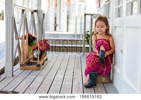 Female Pupil At Montessori School Putting On Wellington Boots
