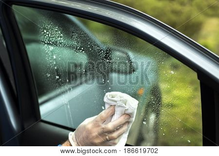 The man's hand wipes the car's glass with a cloth.