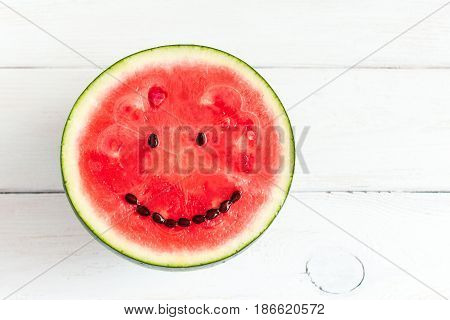 watermelon with smile on white wooden background creative watermelon smile face top view flat lay