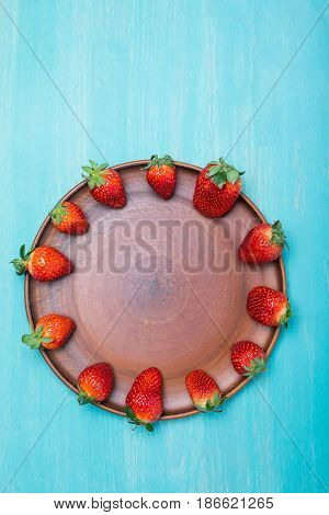 Fresh Red Strawberries In Circle On Ceramic Plate On Blue Wooden Tabletop, Berries Background Concep