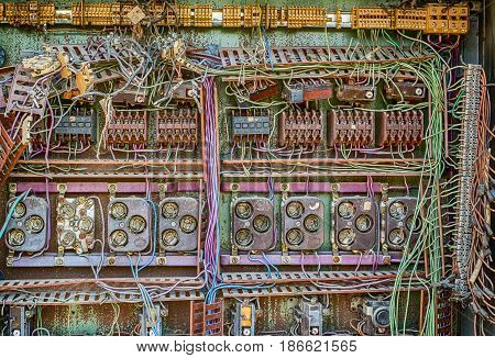 Abandoned electrical panel with wires, closeup view