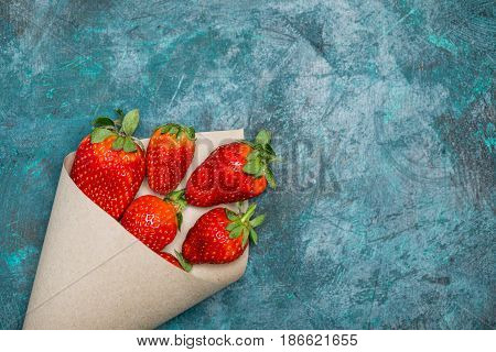 Fresh Red Strawberries Scattered Of Paper Cone On Black Tabletop, Berries Top View Concept