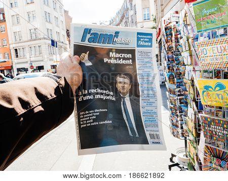 PARIS FRANCE - MAY 15 2017: Man buys L'Ami French newspaper reporting handover ceremony presidential inauguration of the newly elected French President Emmanuel Macron in Paris France