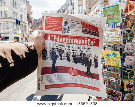 PARIS FRANCE - MAY 15 2017: Man buys L'Humanite French newspaper reporting handover ceremony presidential inauguration of the newly elected French President Emmanuel Macron in Paris France