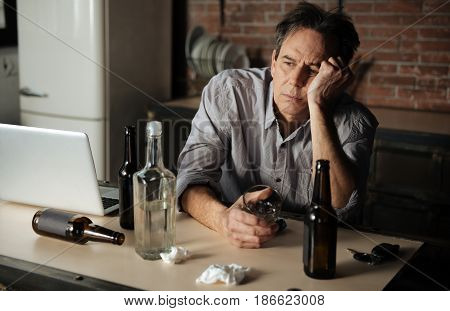 Deep in thoughts. Depressed male person supporting his head putting arms on the table while looking sideways
