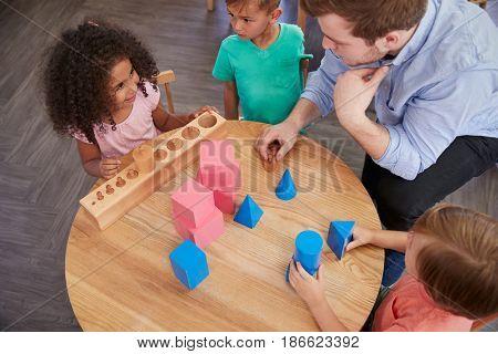 Overhead View Of Teacher And Pupils At Desk In Montessori School
