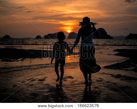 Happy Mother's day and family activity concept. Silhouette of mother holding kind hand and walk on the beach during sunset.