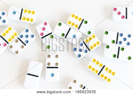 Domino effect shot. Look down for domino game on black background. Dominoes falling in a row in front. Dominoes Game Pieces Isolated on White Background.