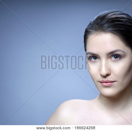 beauty closeup portrait of attractive young caucasian woman brunette on blue background studio shot lips face skin care
