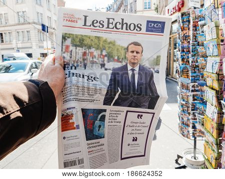 PARIS FRANCE - MAY 15 2017: Man buys Les Echo newspaper reporting handover ceremony presidential inauguration of the newly elected French President Emmanuel Macron in Paris France