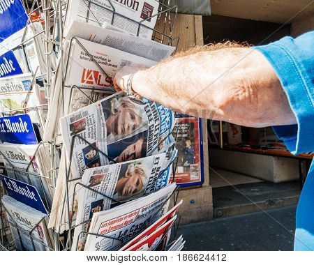 PARIS FRANCE - MAY 15 2017: Senior man buying international newspaper reporting handover ceremony presidential inauguration of the newly elected French President Emmanuel Macron in Paris France
