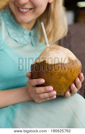 Closeup of woman's hands holding big cocnut and drinking juice with a straw. Girl enjoying drink. Healthy snack and drink. Food concept.