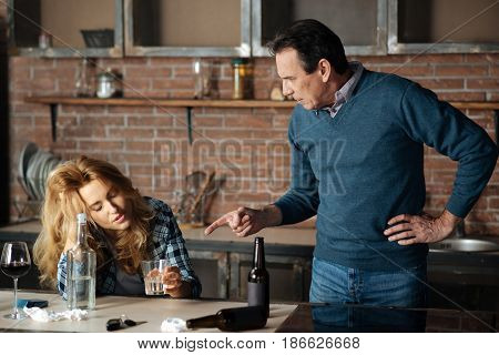 Moral teaching. Frustrated young woman holding glass with vodka in left hand keeping eyes closed while speaking with her husband