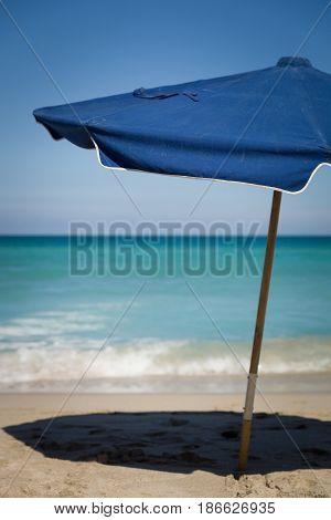 Beach in Miami FL. Open umbrellas on the sand beach at the ocean. Empty beach. Sea shore. Clouds background.
