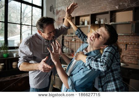 Terrible pain. Strict man wrinkling his forehead and showing teeth while attacking his son