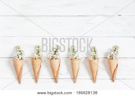 lilac flowers in ice cream cone on white wooden background flat lay top view