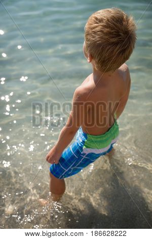Happy boy in flippers standing on the ocean shore on a sunny day. Child going to swim in the sea. Vacations. Activities for child on the beach. Joy and happiness.