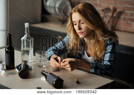 Negative thoughts. Disappointed female person wearing checked shirt looking at her hands while holding plate with tablets