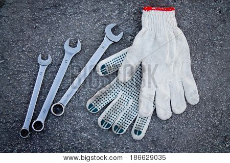 Open-end Wrench And Gloves On The Pavement Background
