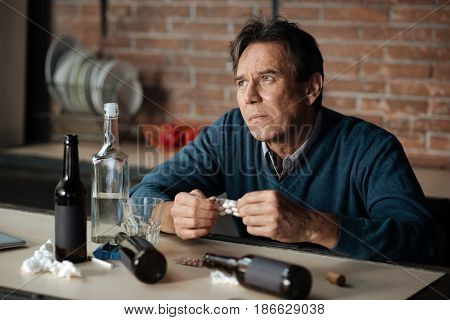 Suicidal ideation. Hopeless male wrinkling forehead holding plate with pills in both hands while sitting at the table