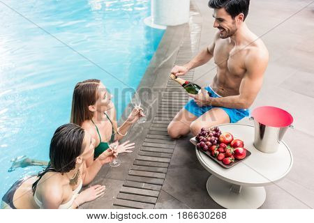 Seductive young man serving with cold champagne and fresh sweet fruits two beautiful women at the swimming pool of a luxury hotel