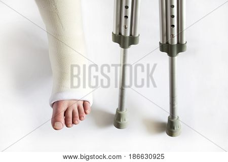 leg in plaster and crutches on white background