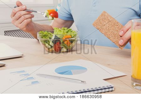 Healthy eating, business lunch in office. Unrecognizable man cropped image, businessman in t-shirt at working place eating salad