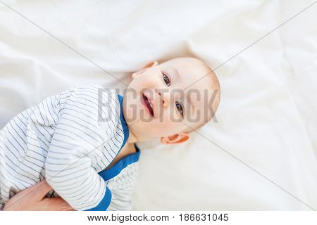 Cropped Shot Of Parent Playing With Adorable Newborn Child Lying On Bed, 1 Year Old Baby Concept