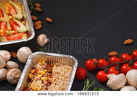 Healthy restaurant food delivery dark background with copy space. Mockup for menu, foil containers with meals on black
