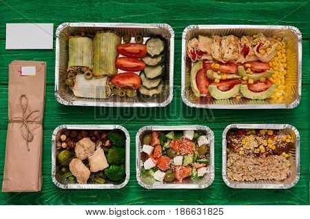 Healthy restaurant food delivery. Take away of natural organic fitness nutrition for diet. Daily meals in foil boxes with copy space at green wood. Vegetables, meat and fruits.