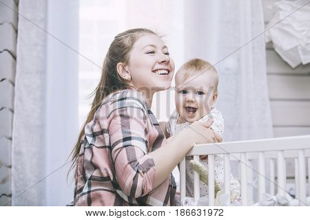 Mother And Little Baby Is In The Crib Woke Up In The Morning And Smiling
