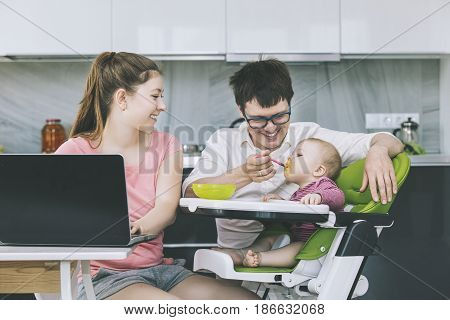 Family Mom And Dad Feeding Baby In The Kitchen Happy Together At Home Smiling