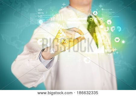 A doctor in white coat with a stethoscope on one shoulder holding a pill with green glowing graphs, lines, numbers, charts, between his fingers