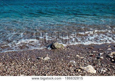 Calm Mediterranean sea. A Sunny summer day. Wave with sea foam.